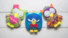 Owls Of Colored Felt On White Wooden Boards