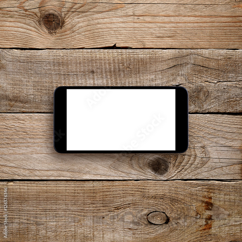Smartphone with blank screen on wooden background. Horizontal view