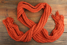 Knitted Orange Scarf In The Shape Of A Heart On A Wooden Background