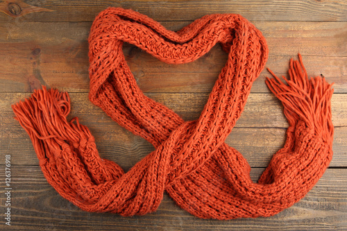 Fotografie, Obraz  Knitted orange scarf in the shape of a heart on a wooden background