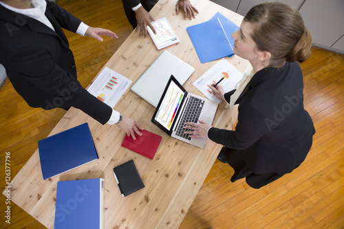 Fototapeta 机を囲んで話すビジネスパーソン obraz na płótnie