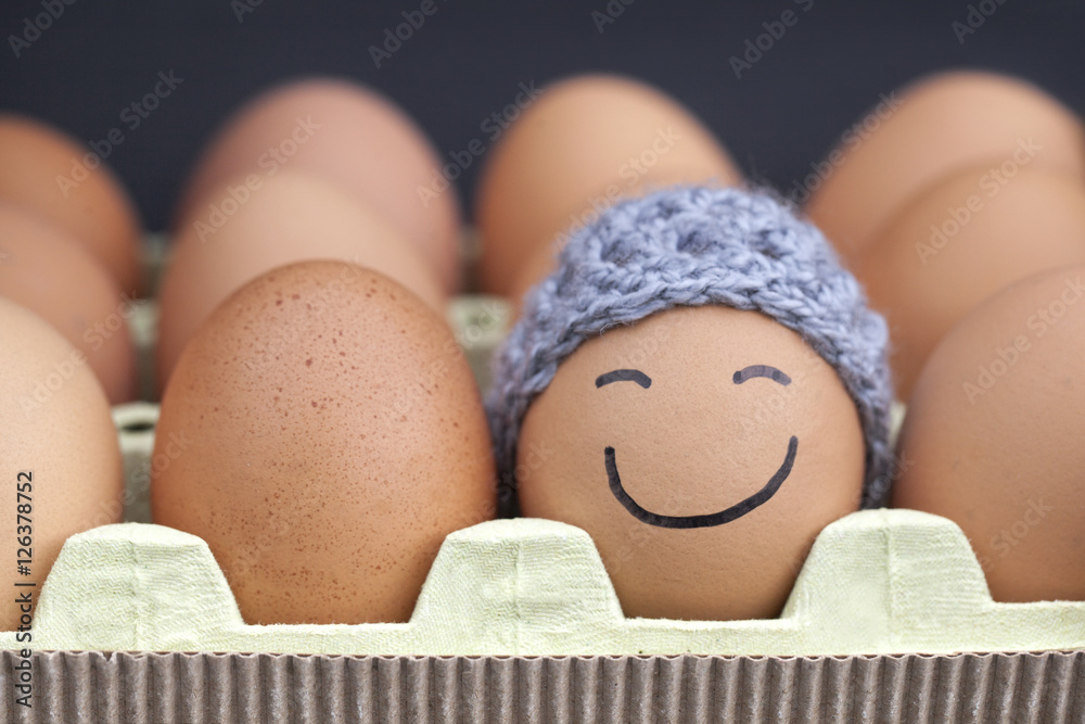 Fototapeta Smiling egg wearing a knitted hat souronded by blank brown eggs.