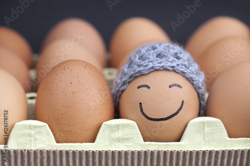 Canvas Print Smiling egg wearing a knitted hat souronded by blank brown eggs.