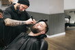Bearded man getting his hair and beard cut at the local barber s