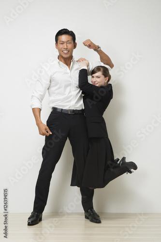 Fotografie, Obraz  マッチョなビジネスマンの腕にぶら下がるビジネスウーマン
