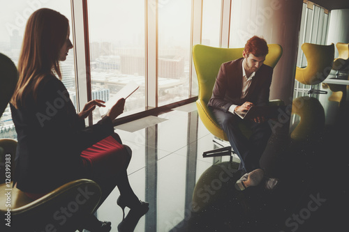 Keuken foto achterwand Muziekband Businessman in formal suite with a laptop and businesswoman in red dress and jacket sitting in front of each other on yellow armchairs in contemporary office interior, view from top of winter city