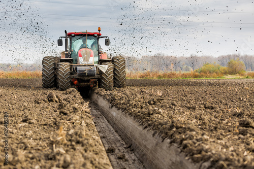 Tractor with double wheeled ditcher digging drainage canal плакат