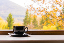 A Cup Of Tea In Front Of A Window With Autumn View.