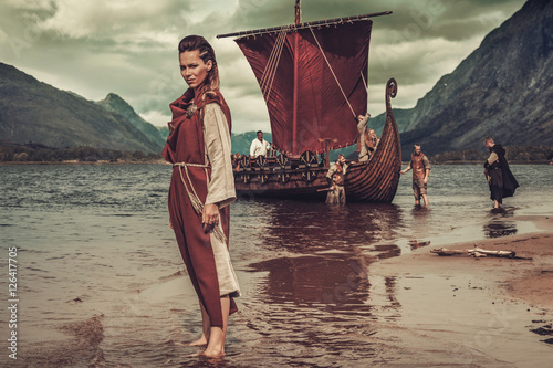 Photo  Viking woman standing near Drakkar on seashore