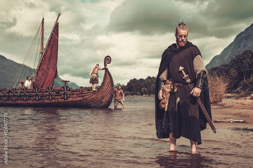 Fotografie, Obraz  Viking warrior with sword standing near Drakkar on the seashore