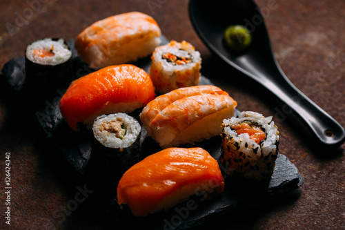 Deurstickers Klaar gerecht Sushi maki rolls and sashimi on a wooden background