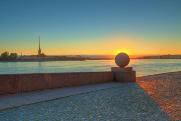 Spit of Vasilyevsky Island and Neva River at dawn with granite ball in front of sunrise, Saint Petersburg, Russia.