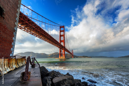 Golden Gate Bridge in San Francisco on a partly cloudy day Poster