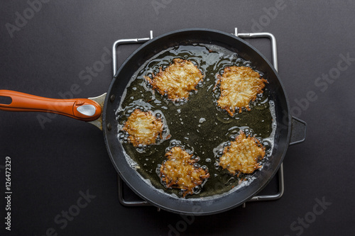 Fotografía  Frying latkes with ready side up in deep oil on the pan from above