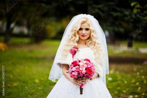 Fotografie, Obraz  Portrait of charming blonde bride in a fur coat with bouquet