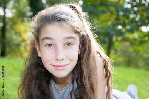 Pretty brunette preteen brunette girl in the forest smile