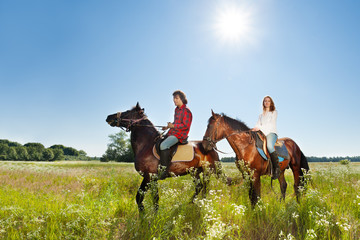 Young couple spending time together riding horses