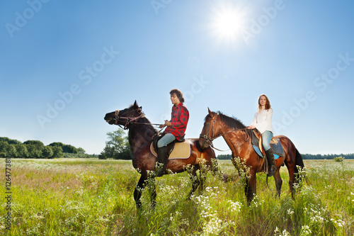 Poster Equitation Young couple spending time together riding horses