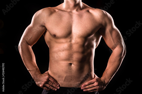 Fotografie, Obraz  bodybuilder upper body below the neck isolated with black background