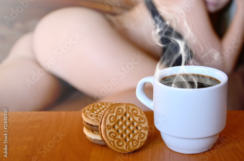 A Cup Of Hot Coffee And Round Cookies With Silhouette Y In Black Underwear The Background On Bed Focus Foreground Priority Small White