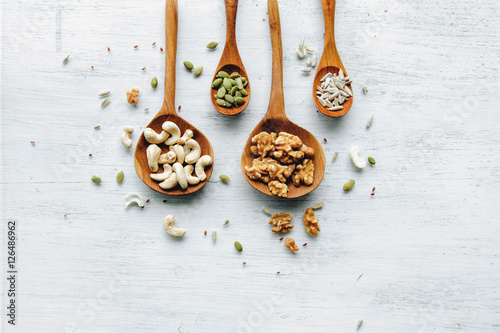Four wooden spoons with seeds and nuts on thw white table