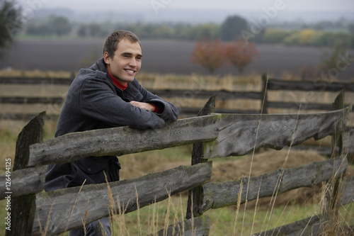 Fototapety, obrazy: Young man leaning on country fence