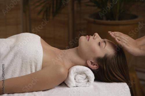 Photo  Young woman receiving reiki massage