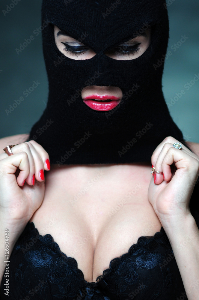 Fototapeta girl in bra and balaclava - black and white photo in studio of a psycho girl terrorist