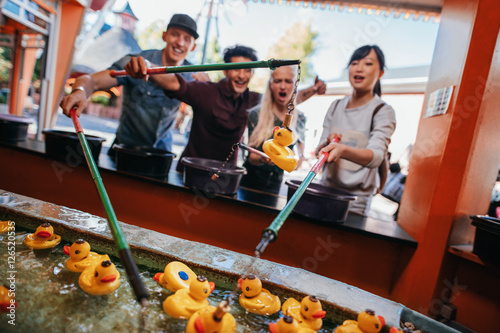 Poster Amusementspark Group of people playing fishing game at amusement park