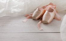 Pink Ballet Pointe Shoes And Tutu On White Wood Background
