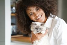Portrait Of Mixed Race Woman Cuddling Cat