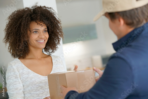 Mixed race woman receiving package from delivery man Tapéta, Fotótapéta