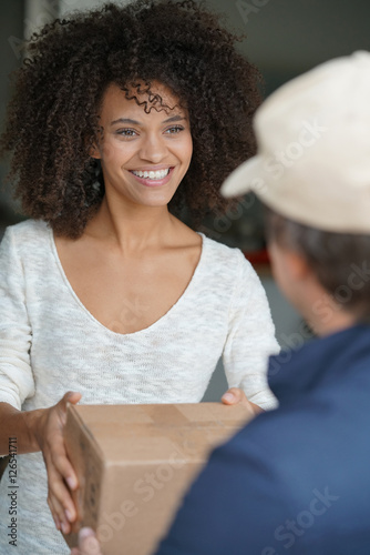 Fényképezés Mixed race woman receiving package from delivery man
