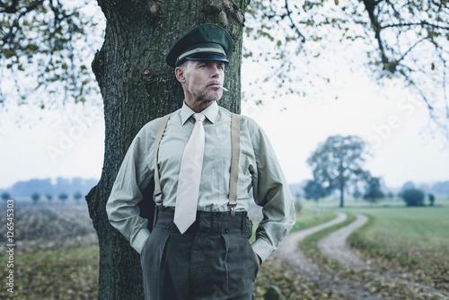 Retro 1940s military officer smoking cigarette under tree. Canvas Print