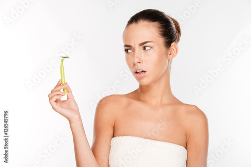 Woman with pure skin holding razor blade preparing to shave