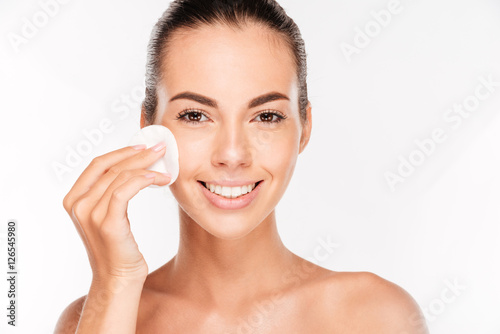 Foto  Young beautiful cleaning face with cotton pads