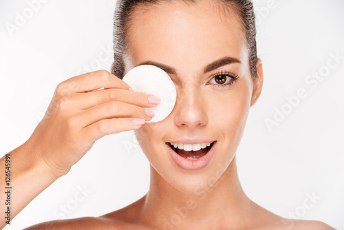 Foto  Laughing woman holding round white cotton pad to her eye