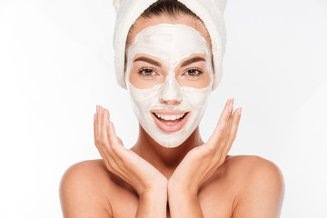 Fototapeta Do Spa Beautiful smiling woman with white clay facial mask on face