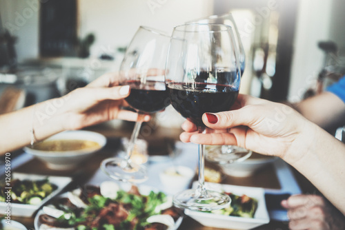 Fotografie, Obraz  Young happy friends cheering with glasses of red wine, family dinning at home, e