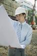 Businessman wearing hardhat, looking at blueprints