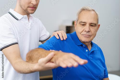 Fotografía  orthopäde untersucht die schulter eines älteren patienten