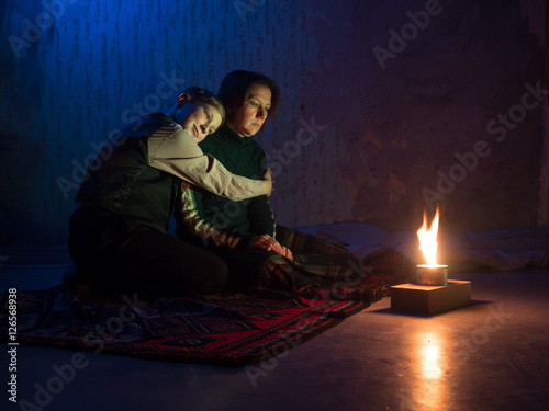 Adult woman sitting on the floor and crying and the young boy put his head on th Canvas Print