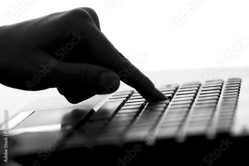 Fototapety, obrazy: silhouette of the finger of a female hand press a key on the keyboard of the netbook