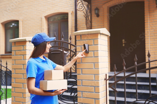 Fényképezés Female courier in uniform ringing in doorbell