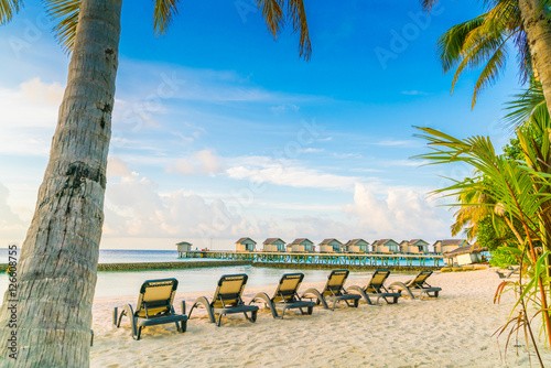 Poster Strand Beach chairs in Maldives island with water villas at the sunrise