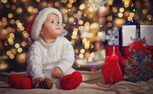 Little Boy In Christmas Santa's Hat, Against The Backdrop Of A C