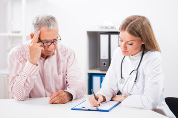 Doctor is writing prescription to her patient.