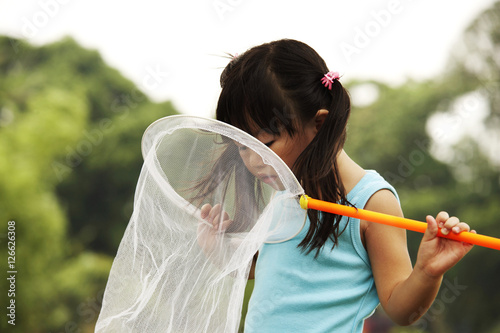 Photo  girl looking into butterfly net