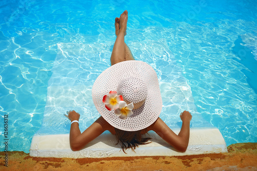 Obraz na plátne young woman in big white hat rested on a lounger in the pool