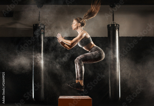 Fotografie, Obraz  sporty girl jumping over some boxes in a cross-training gym